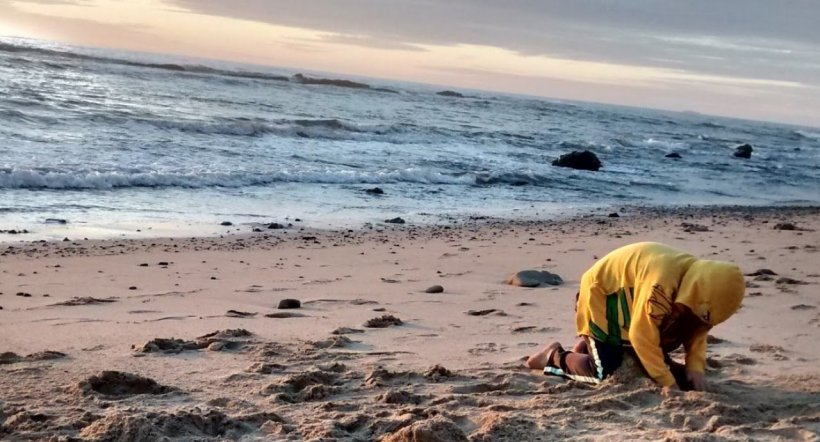 Child digging in sand on beach